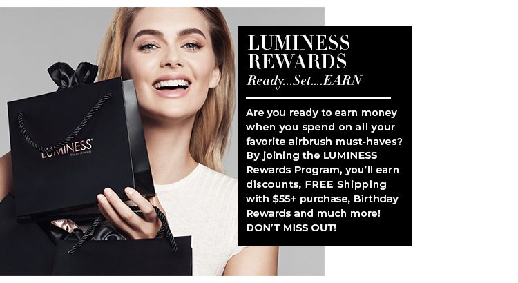 Caucasian model, smiling holds a black Luminess shopping bag